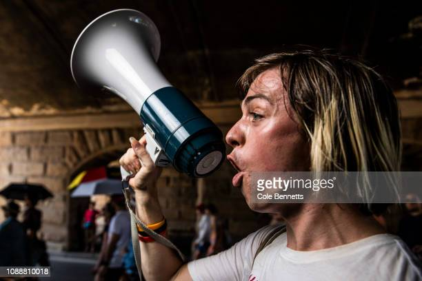 A young man screams protest chants into a megaphone as tens of thousands take to the streets of the CBD for the Invasion Day March on January 26 2019...
