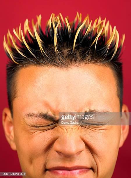 Young man scrunching face, close-up