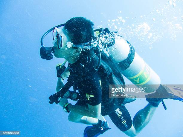 Young man scuba dives with nitrox in bunaken Sulawesi Indonesia