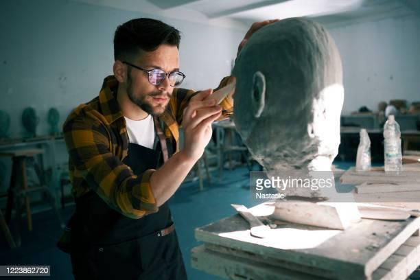スタジオで粘土から頭を彫刻する若い男 - 彫刻家 ストックフォトと画像