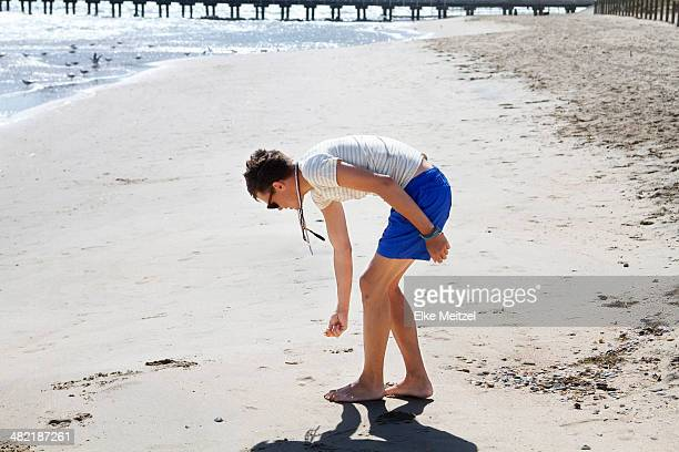 Young man searching for seashells on beach, Port Melbourne, Melbourne, Australia
