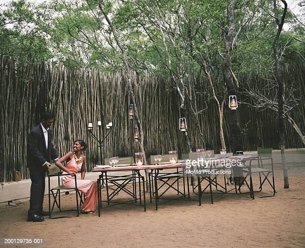 Young man seating woman at outdoor dining table at safari lodge