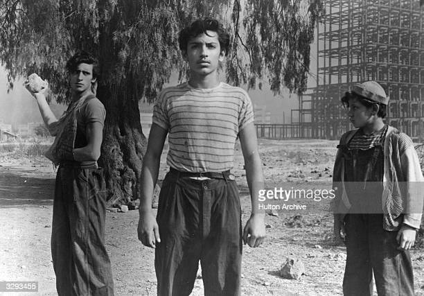 A young man seems oblivious to the fact that he is about to have a rock thrown at him in a scene from Luis Bunuel's Mexican film 'Los Olvidados'...