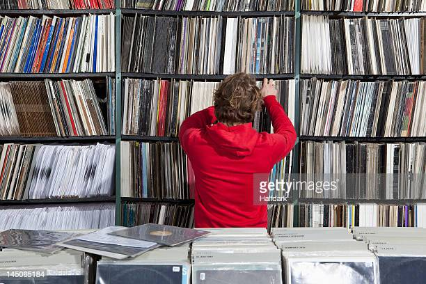 A young man selecting a record from a shelf in a record store