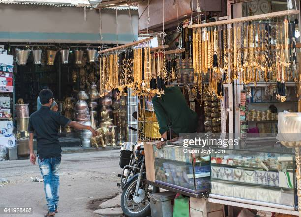 Young man selling Indian style golden ornament in local market.
