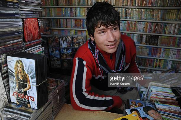 A young man sells film and music DVDs in a kiosk on the street side on October 15 2011 in Kabul Afghanistan A DVD of best of Shakira is placed on his...