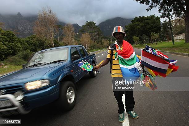 1bbd49fd005 A young man sells football merchandise at the side of the road into central Cape  Town. Editorial use only