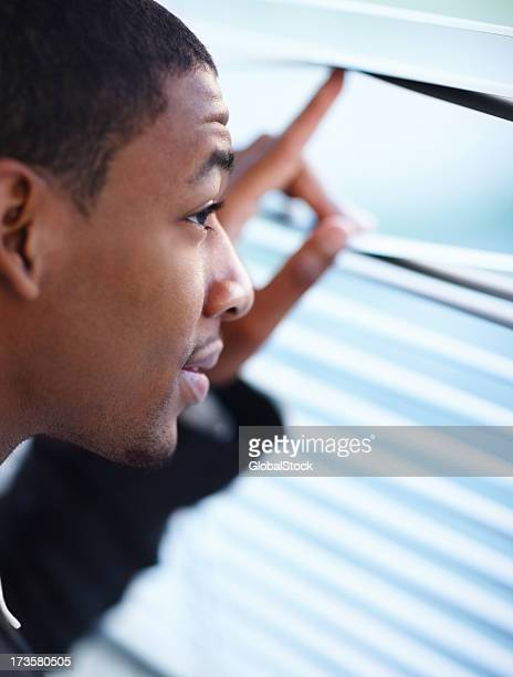 Young man separating blind sheets and looking out
