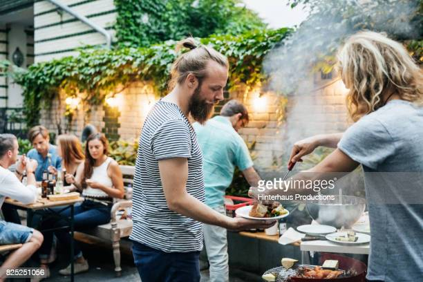 young man serving his friend food from barbecue - man bun stock pictures, royalty-free photos & images