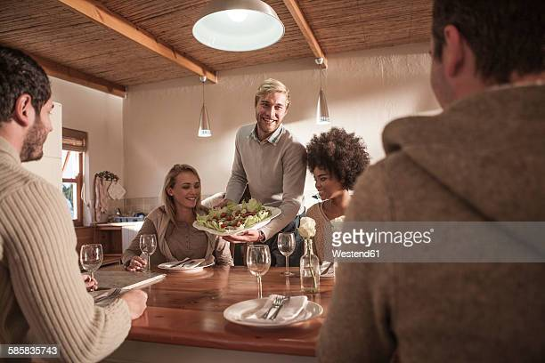 Young man serving plate with salad for friends