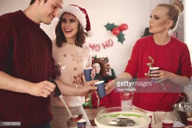 Young man serving punch to friends at christmas party