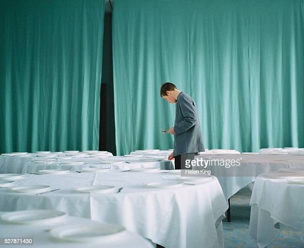 young man setting tables in a banquet hall - banquet hall stock pictures, royalty-free photos & images