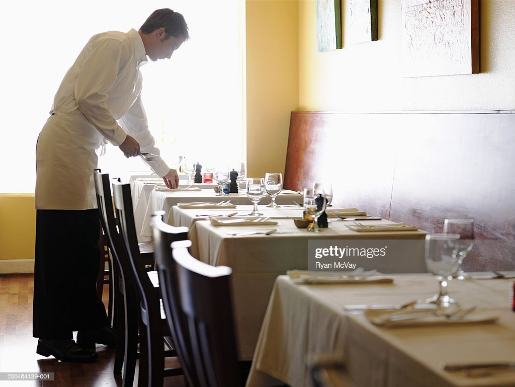 Young Man Setting Tables In Restaurant Side View High-Res ...