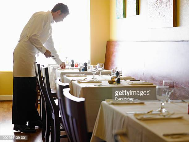 young man setting tables in restaurant, side view - waiter stock pictures, royalty-free photos & images
