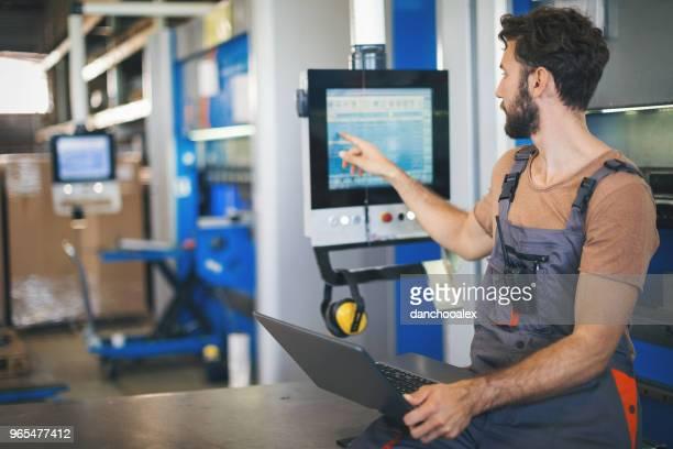 junger mann, die einstellung der maschinen in der fabrik - rechnerunterstützte fertigung stock-fotos und bilder