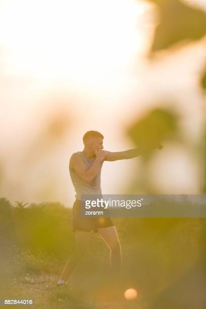 Young man shadow boxing outdoors