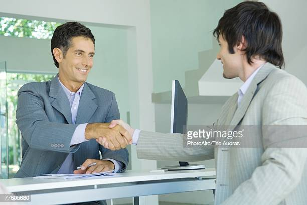 Young man shaking hands with mature businessman across desk, smiling