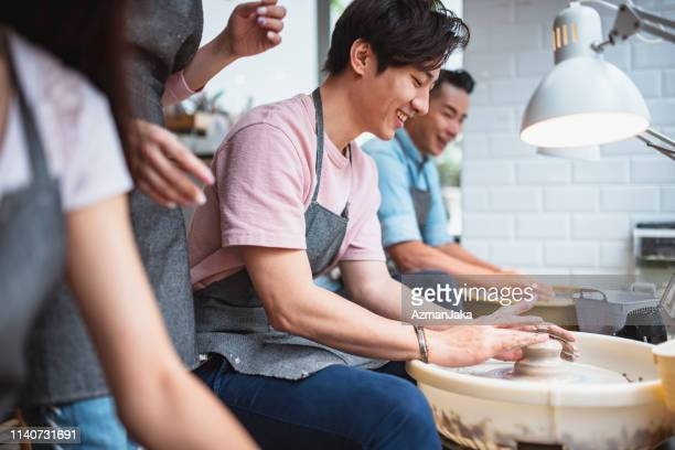 young man shaping clay in a pottery class - pottery stock pictures, royalty-free photos & images