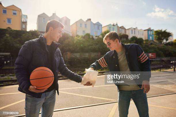 Young man sharing bag of chips with friend, young man holding basketball, Bristol, UK