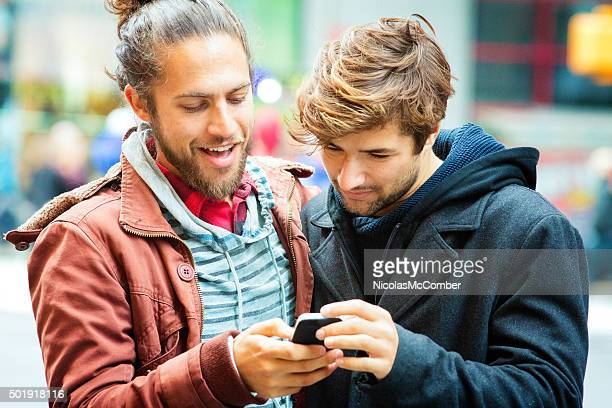 Young man sharing media with friend on mobile phone close-up