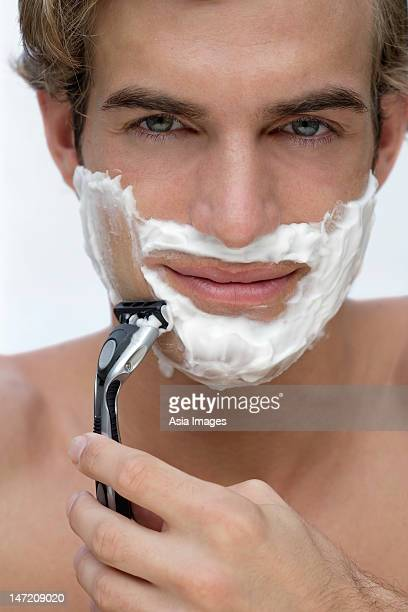young man shaving face