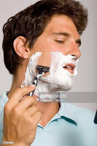 Young man shaving, looking away, close-up