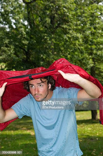 Young man sheltering from rain under jacket