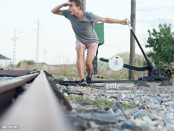 Young Man Shielding Eyes While Pulling Lever Of Railroad Switch Stand