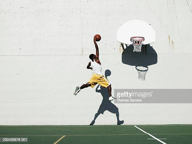 Young man shooting at basketball hoop on outdoor court, side view