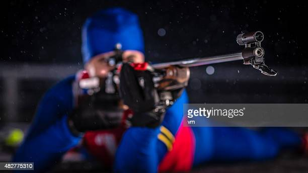 Young man shooting at biathlon training at night