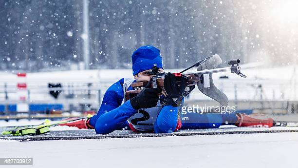 Young man shooting at biathlon training