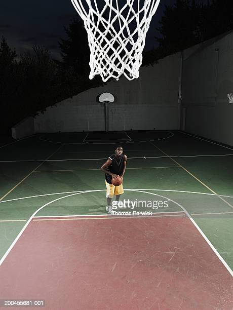 young man shooting free throw on outdoor basketball court, night - tiro libre encestar fotografías e imágenes de stock
