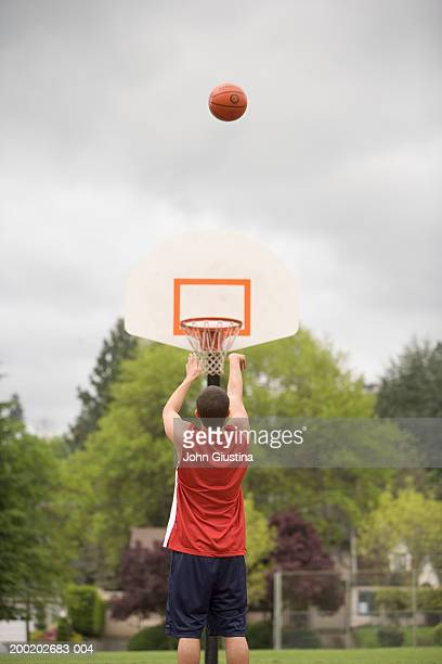 young man shooting free throw, rear view - shooting baskets stock pictures, royalty-free photos & images