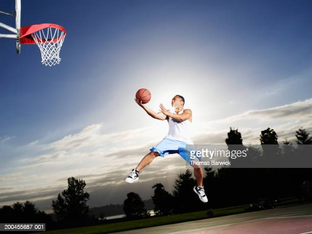 Young man shooting layup on outdoor basketball court at sunset