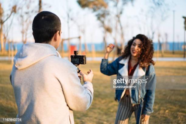 若い女性のためのビデオを撮影する若い男 - ルポルタージュ ストックフォトと画像
