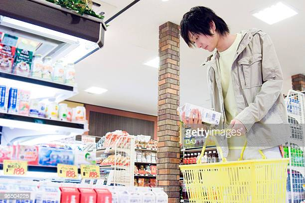 young man shopping at supermarket - milk carton stock photos and pictures