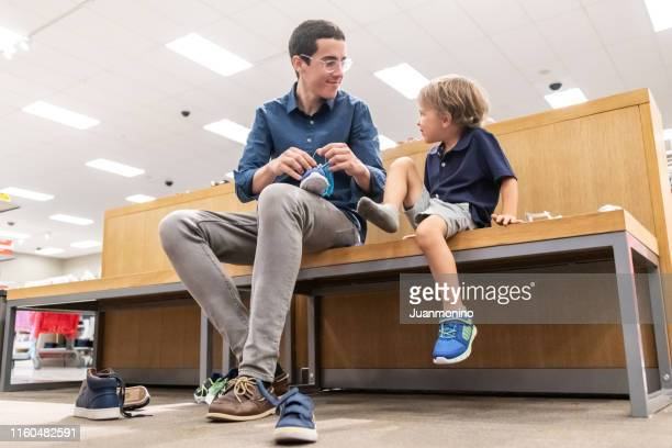 young man shopping for shoes for his son - shoe store stock pictures, royalty-free photos & images