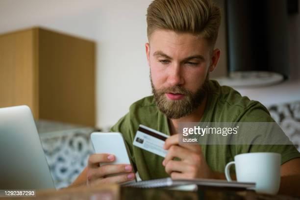 joven comprando en línea - izusek fotografías e imágenes de stock