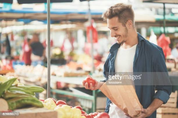 Junger Mann einkaufen Tomate