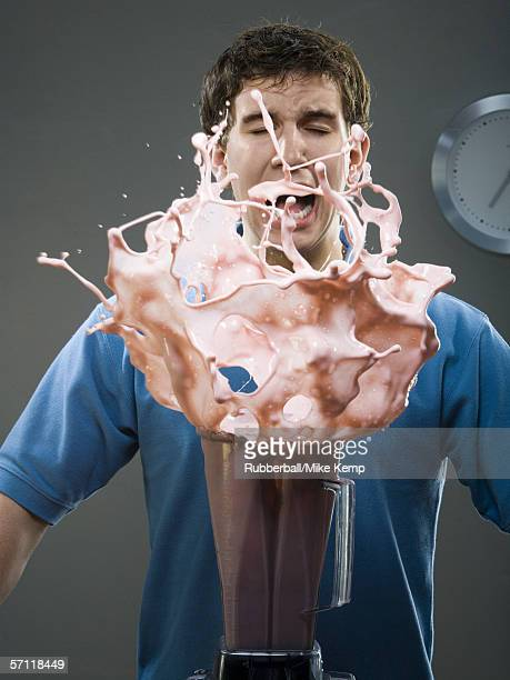 Young man shouting as milk shake spills out of a blender