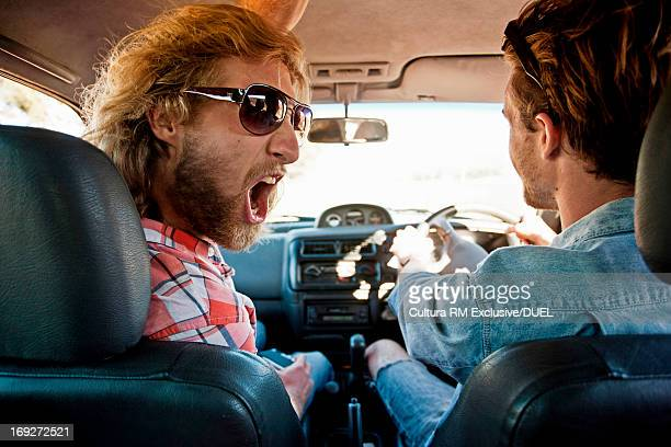 Young man shouting to driver on road trip