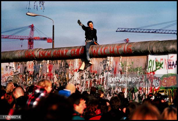 A young man shouts as he sits astride the Berlin Wall while crowds mill about on the ground below November 10 following the opening of the famous...