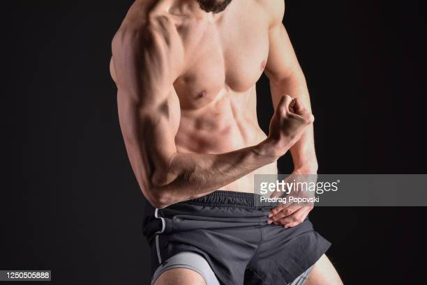 young man showing his bicep chest and abdomen muscles over dark studio background - 男らしさ ストックフォトと画像