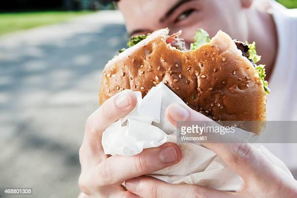 Young man showing his hamburger