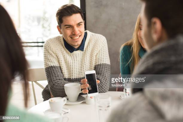 young man showing his mobile phone in cafe - showing off stock photos and pictures