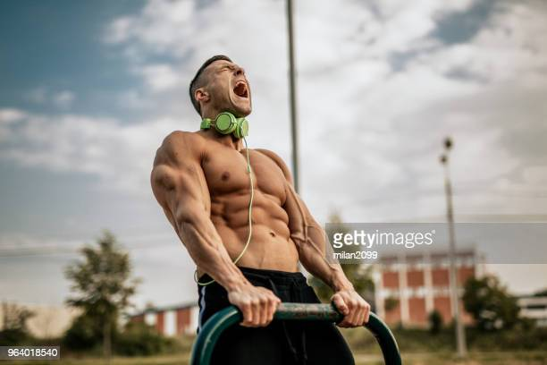 young man showing his muscles in the local park - masculinity stock pictures, royalty-free photos & images