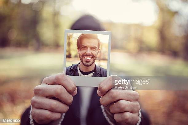 Young man showing instant photo