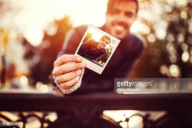 young man showing instant selfie - seulement des adultes photos et images de collection