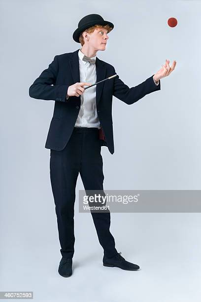 Young man showing magic with ball