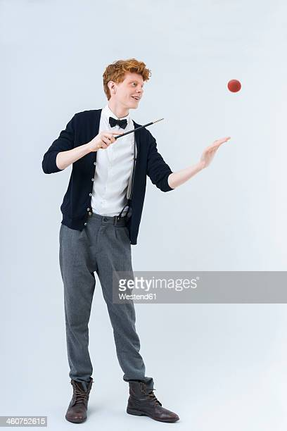 Young man showing magic with ball, smiling